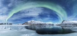 A wide shot of the arch shaped northern lights over a frozen sea with the snow covered mountains in the background