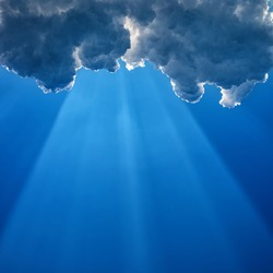 A wide sunray breaks through dark cumulus clouds on a blue sky background, square frame