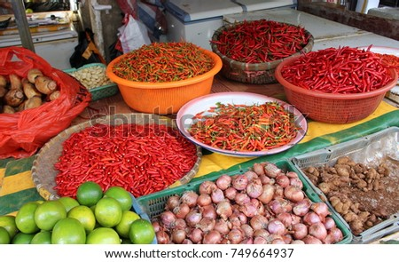 A wide variety of fresh red chili peppers of local varieties on the street market in China. In the foreground lie the fruits of lime, onions and ginger. There is no merchant behind the counter. #749664937