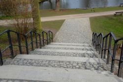 a wide walkway in the park leads directly from the slope down to the pond. has a black metal railing on the handrails. stone and concrete paths and stairs