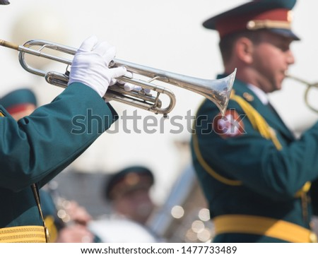 A wind instrument parade - a man in green costume playing trumpet #1477733489