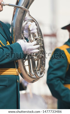 A wind instrument parade - a man in green costume playing tuba #1477733486