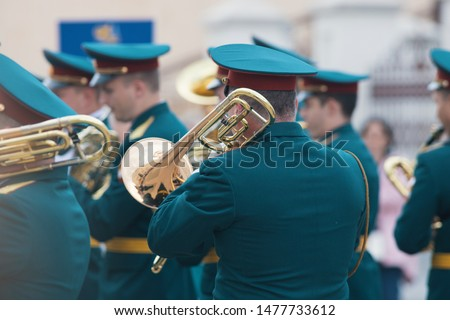 A wind instrument parade - man in green costumes holding a trumpet and playing it #1477733612