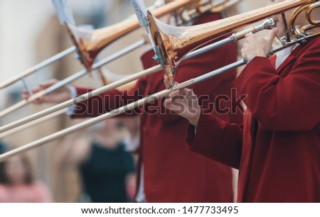 A wind instrument parade - men in red costumes playing trumpet #1477733495
