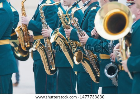 A wind instrument parade - people in green costumes holding saxophone #1477733630