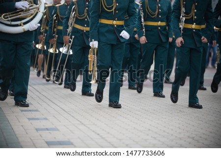 A wind instrument parade - people in green costumes marching #1477733606