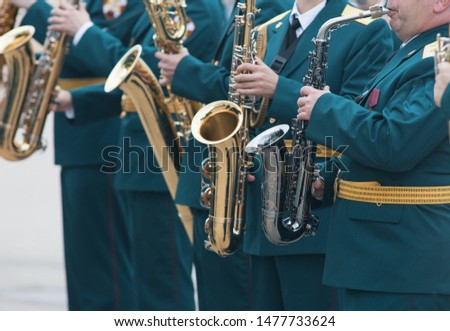 A wind instrument parade - people in green costumes playing saxophone #1477733624