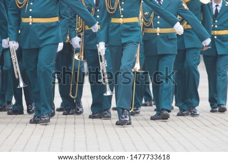 A wind instrument parade - people in green costumes walking on the street holding musical instruments #1477733618