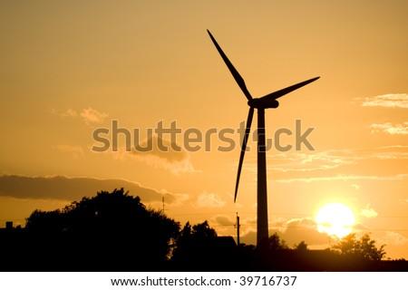 A wind turbine at sunset.