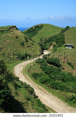 a winding dirt road between the hills