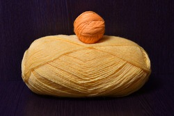 A winding of yellow yarn and a tangle of orange yarn lie on a dark brown table.