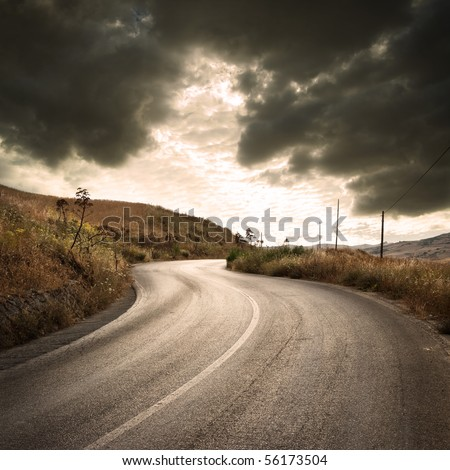 a winding road in countryside with gloomy cloudscape at the sunset