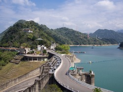 A winding road next to Shihmen Reservoir in Taiwan. This reservoir is the third largest reservoir or artificial lake in Taiwan. Translation of text: