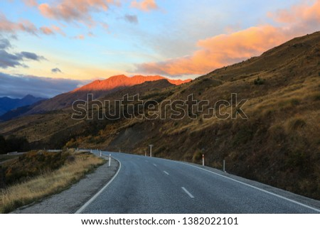 A winding road through the mountains during the daytime sunlight shows the summit #1382022101