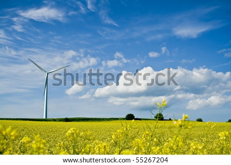 A windmill in a rapeseed field on a background of blue sky