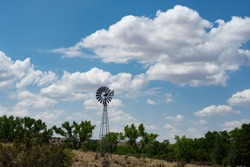 A windmill on a hill with green trees and a bight blue sky with white clouds