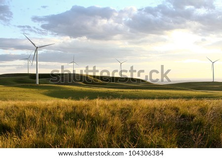 A windmill on a hillside silhouetted by a sunset