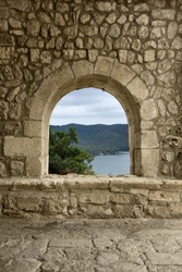 A window/arch at the entrance of a romanesque church in a spanish village. A beautiful landscape may be seen through it.