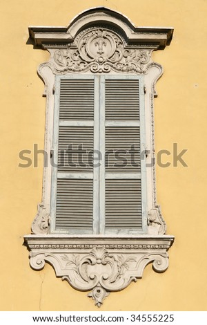 "A window at a classical house in the typical regional color, ""yellow of Parma"""