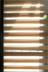 A window glass which is covered with brown striped window curtain for blocking the sunrays.