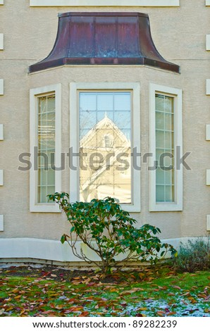 a window in shadow reflecting modern house building at winter with patches of snow at lawn - stock photo