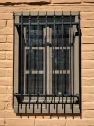 A window of old mud brick with ornamental iron bars.