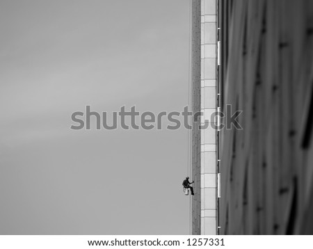 A window washer dangled precariously at the end of a long rope.