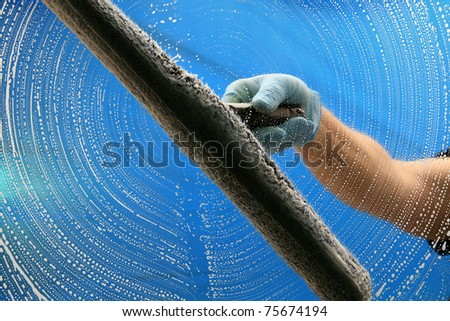 a window washer soaps and cleans a window with a squeegee with room for your text