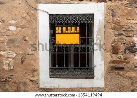 A window with a For Rent sign in the old town of Caceres, Extremadura, Spain.