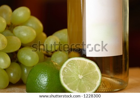 A wine bottle with green grapes and limes.