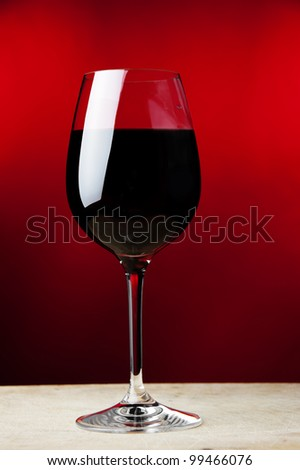a wineglass filled with red wine at red background