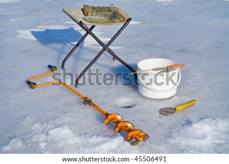 A winter fishing on ice, equipment: auger, camp-chair, ladle, mittens, bucket and rod.