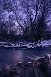 a winter forest river flows through the stone cascade in the evening blue-purple twilight with snow, bare trees and silky water. shot with a long exposure