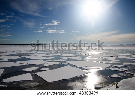 A winter landscape in the sunlight with packed ice in the sea.