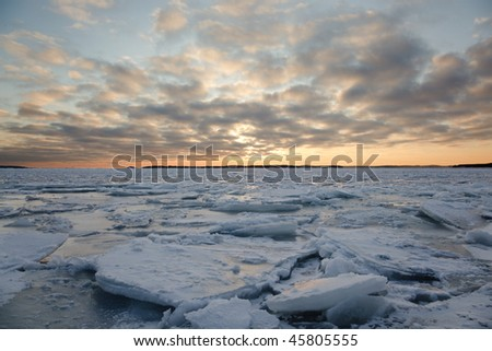 A winter landscape in the sunset with packed ice in the sea.