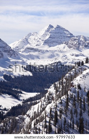 A winter landscape view, in vertical format, of the two peaks in the Maroon Bells massif in Colorado.