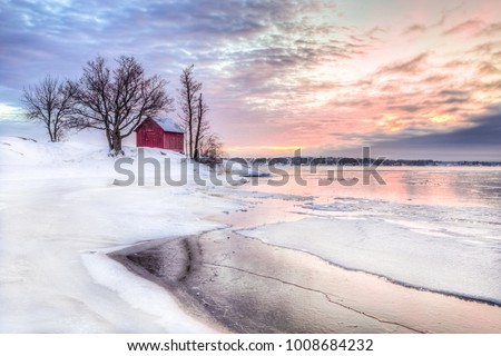 A winter photo of a red little cottage with some trees in the archipelago of Stockholm, Sweden. There is snow on the ground and some ice on the lake. The sky is colored from the beautful winter sunset