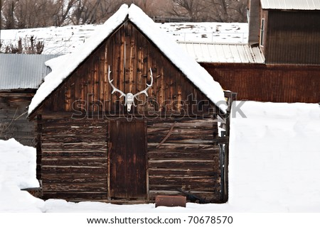 A winter scene in the western US with old an barn, elk antlers, and other farm buildings/