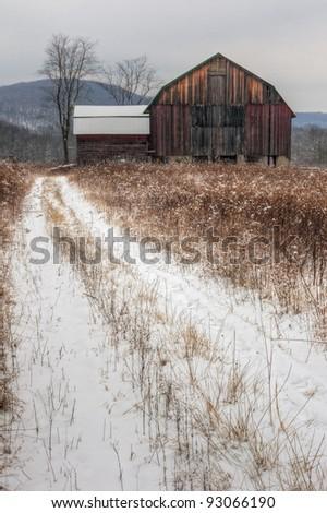 A winter snow scene of a rustic old barn.