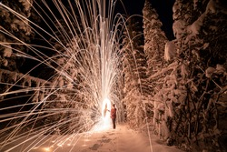 A winter snowy tree, forest, woods landscape with amazing sparking, steel wool effect shooting sparks across the frozen landscape at night. Unique background, wallpaper abstract view.