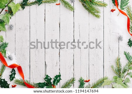 A winter style frame of ivy, holly, fir tree branches and white painted pinecones with ribbon around a central copy space on a white wooden rustic background.  #1194147694