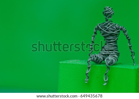 A wire frame figure of person sat on a ledge #649435678