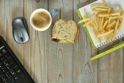 A wireless mouse, fried potatoes, cup of coffee, piece of bread and notebook with pen isolated on a wooden surface - work at home concept