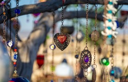 A wish tree in Cappadocia and a necklace with a heart hanging from the tree.