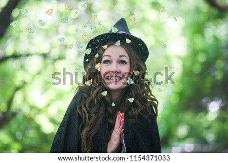 a witch cute witch. attractive girl in a cap. butterflies flying. Halloween Holiday #1154371033