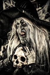 A witch holding a skull. Halloween. Horror movie.