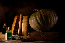 A witch's desk with magic potions, pumpkin and old books
