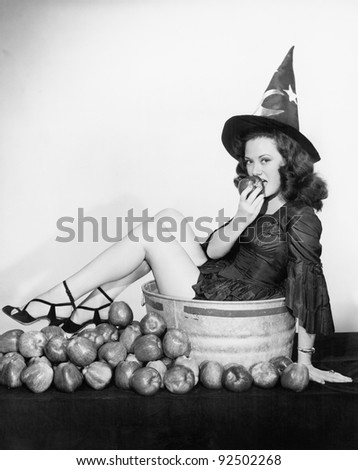 A wizardly woman takes a bite out of a big apple
