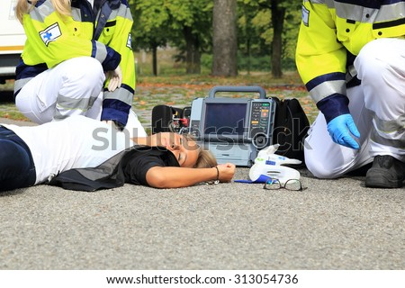 A Woman after Accident with paramedic and defibrillator first aid
