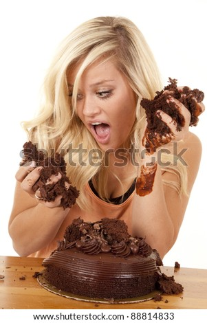 a woman after digging into a chocolate cake getting ready to take a bite.